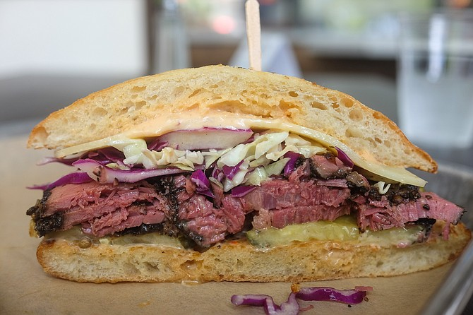 A Reuben-like sandwich with a house pastrami of hickory-smoked brisket, served on a ciabatta.