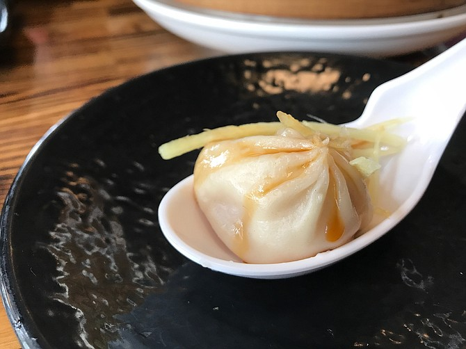 Xiao Long Bao on a spoon with fresh ginger