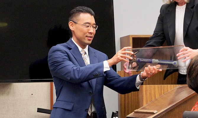 Prosecutor Keith Watanabe w the bloody hammer, sealed in container during trial. Photo by Eva.