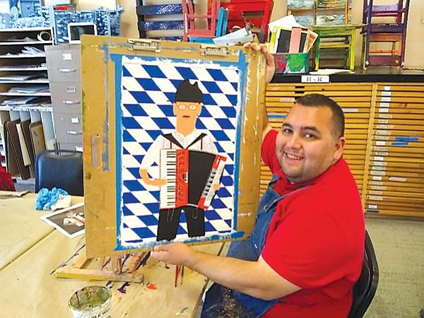 Charlie Lizarraga works on a logo for the German-American Club's Oktoberfest.