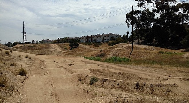 The proposed housing site, where local youth come to ride their bikes, abuts the Park Point Loma townhomes (background)