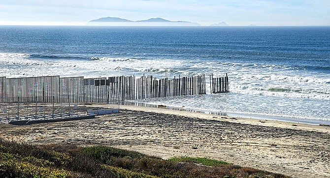 Border Patrol requests San Diego and Imperial Beach Lifeguards for two people holding on to border fence in the water.