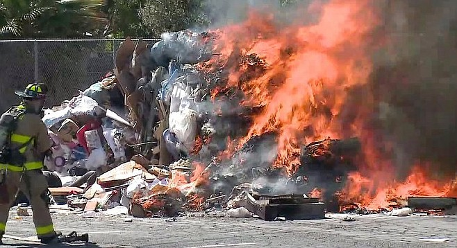 A San Diego firefighter moves to douse the garbage fire. The cause of the blaze is as yet unknown, but it's probably something to do sexual harassment or national politics, or both.