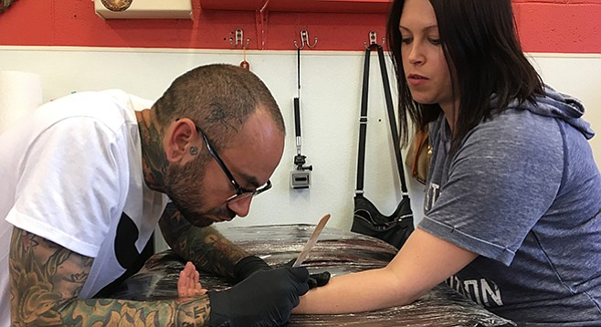 Phil Mayhew touches up Sarah Kahn's arm tattoo at Primos Tattoo in Escondido