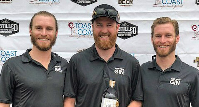 Jordan Kohn, Justin Wilkinson, and Ryan Kohn celebrate their gold medal gin. Photo courtesy Pier View Gin.