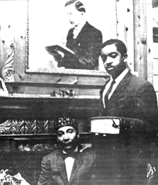 Elijah Muhammad and son Wallace under photo of W.D. Fard