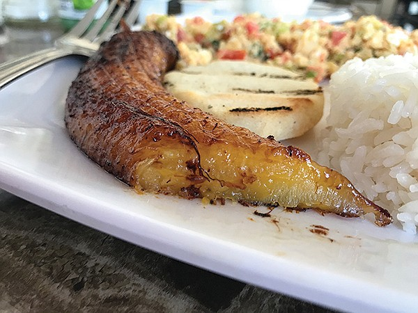 Plantain, with rice, a disk of arepa, and breakfast eggs.