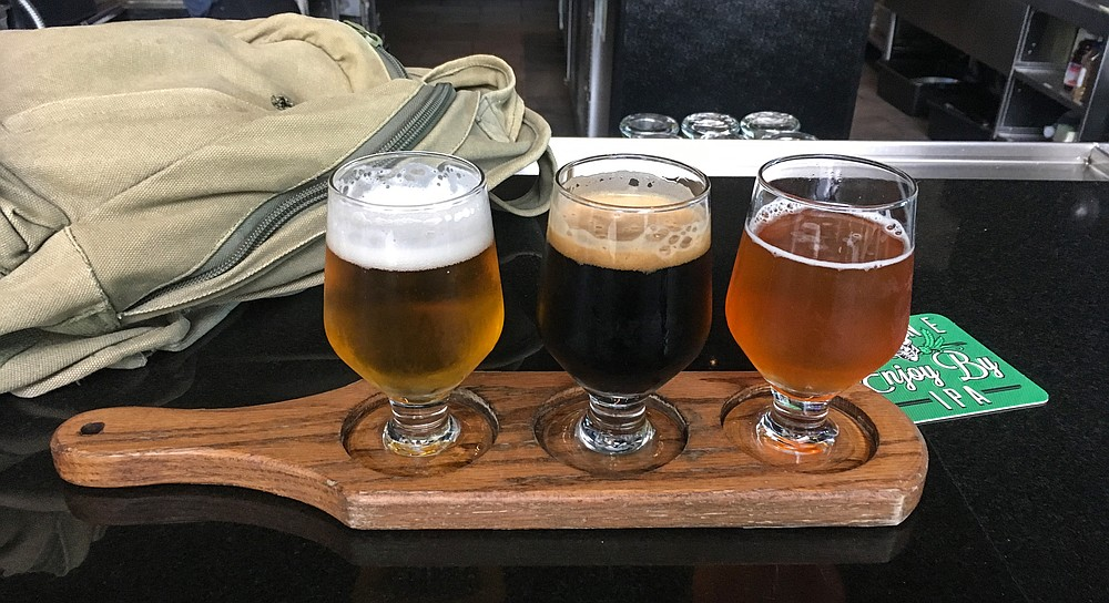 A carry-on bag and flight of Stone Hoppy Lager, Cimmerian Portal stout, and I'm Peach double IPA.