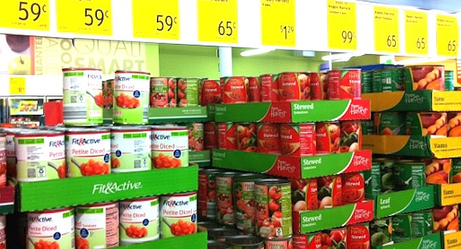 Grocery items are shelved directly in the product's cartons or open boxes.