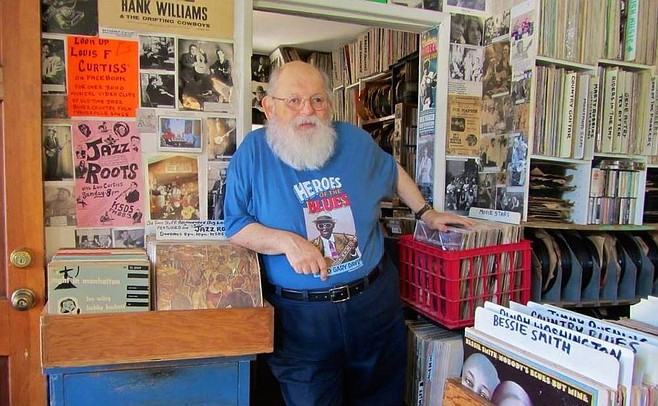 Lou Curtiss manning the record store in his Robert Crumb-drawn T-shirt (http://www.folkartsrarerecords.com)