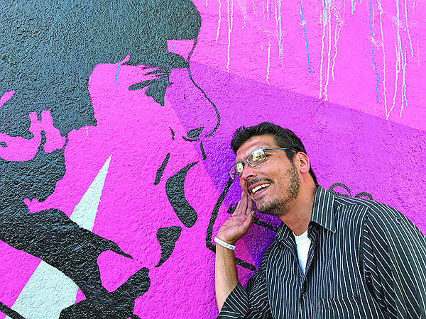 Carlos Quezada listens for a mural message