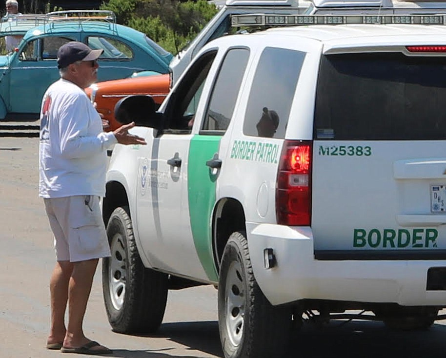 Imperial Beach resident Tom Summers talks to Border Patrol. He drove his turkis colored 1962 VW Bus up to meet with the caravan.