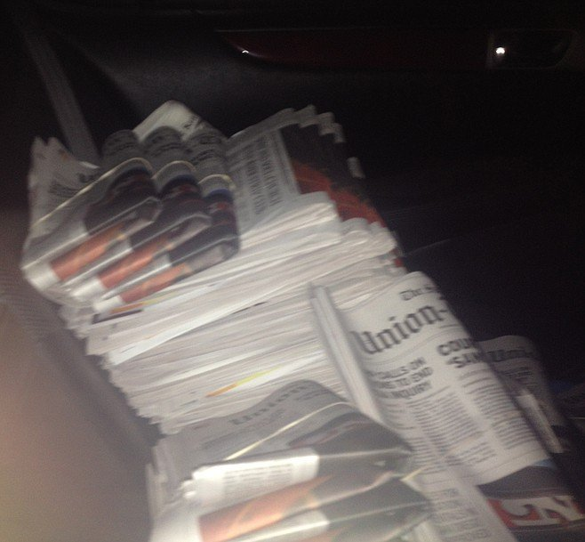 In the back of Bob's Lexus, I'm surrounded by newspapers that need folding.