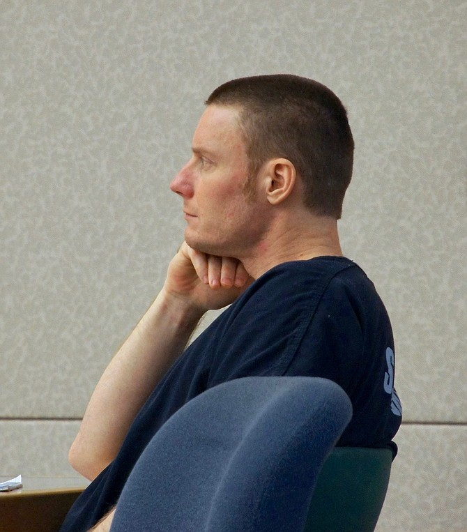 Defendant in courtroom observing evidence. Photo by Eva Knott.