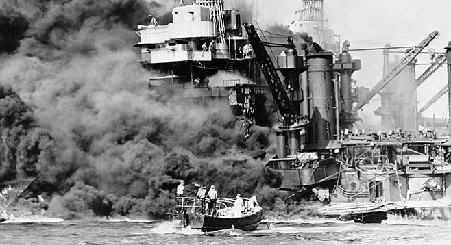 Sailors in a motor launch rescue a man overboard alongside the burning USS West Virginia during or shortly after the Japanese air raid on Pearl Harbor.