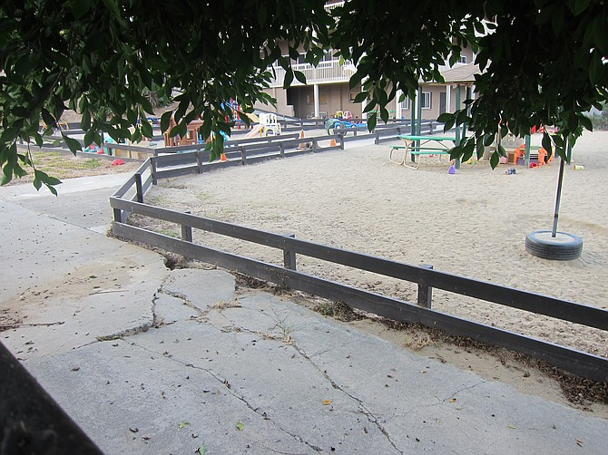 The sidewalk between the tree and the fenced playground is indeed messed up.