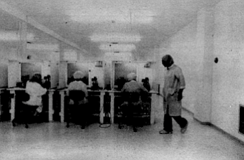 """The """"clean room."""" Forty Mexican women dressed in white smocks, white caps, even white booties, toil in an all-white room behind a large picture window."""