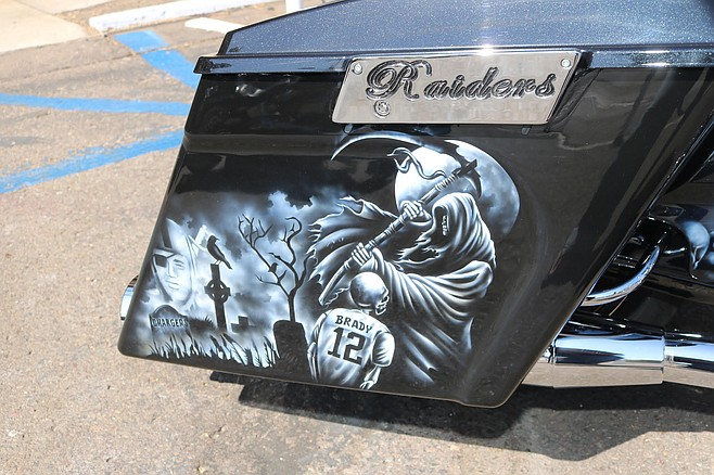 A female fan was posing on a motorcycle with an airbrush design of a Chargers' gravesite headstone.
