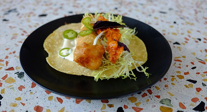 Battered and fried thresher shark with chipotle tomato sauce, jalapeños, and frisée