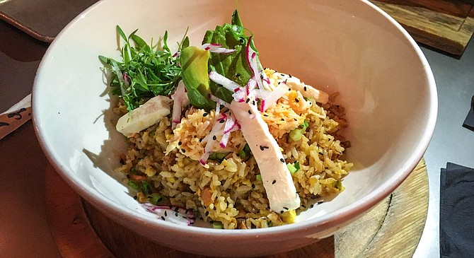 Sliced bits of cream cheese in a Mexican styled fried rice, along with spicy crab, avocado, micro cilantro