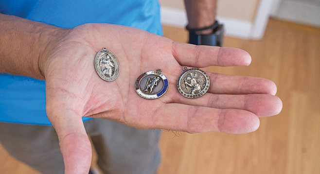 Donald Carr's St. Christopher Medal and more medals from Vietnam in Antonio Palma's hand. - Image by Matthew Suárez