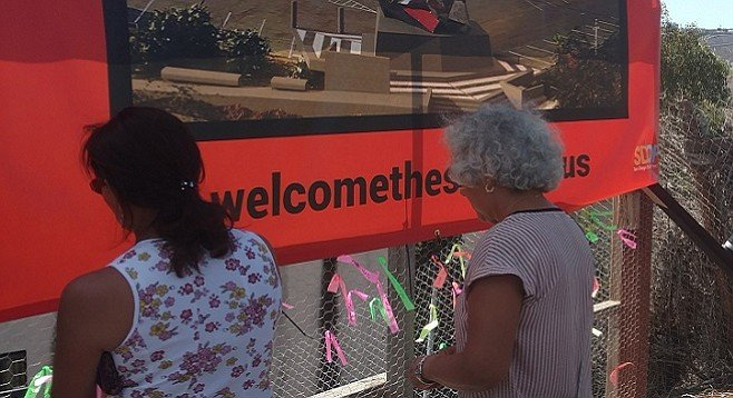 Project supporters tie ribbons with the names of loved ones affected by immigration issues to a fence near the statue's future home