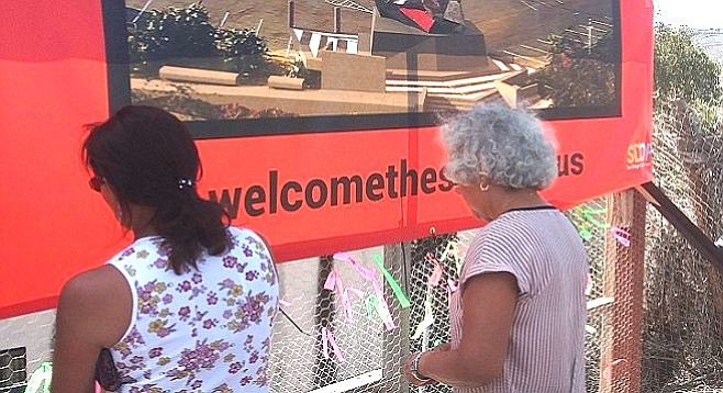 Visitors tie ribbons to fence surrounding project.