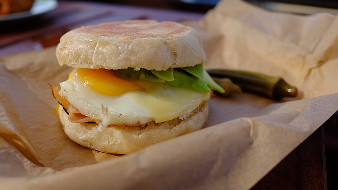 Ham and avocado egg sandwich in a Wayfarer English muffin, served alongside a cup of joe made with beans from Encinitas's Ironsmith Coffee Roasters.
