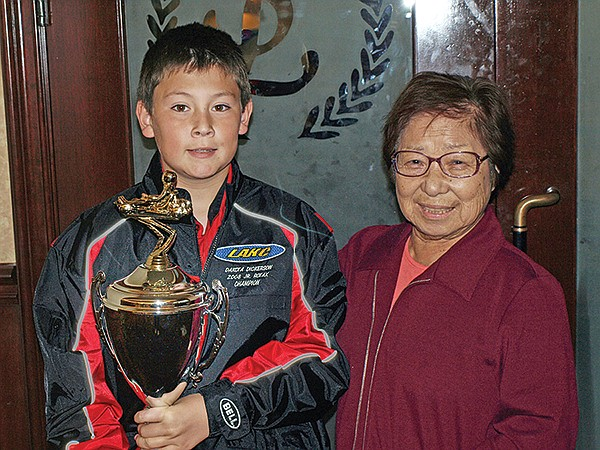 Dakota Dickerson standing with a go-kart racing prize with his also-racing grandma, Kimiko, known as Kim