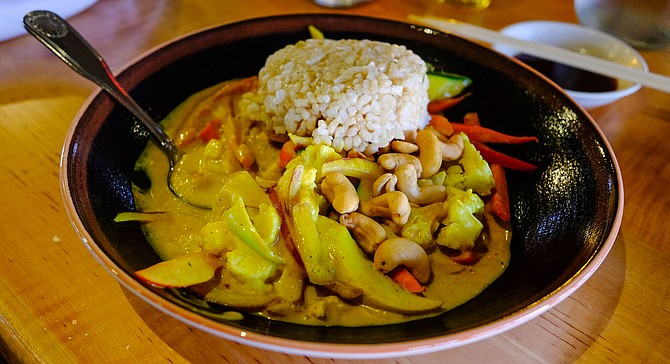 A yellow coconut curry with cashews and vegetables
