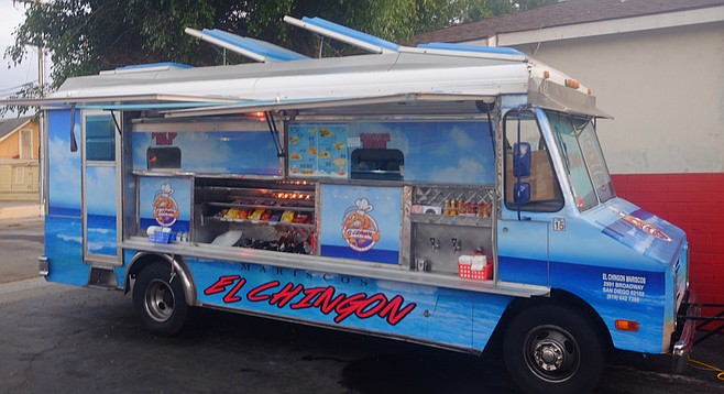 A mariscos truck in the parking lot of a barber shop.