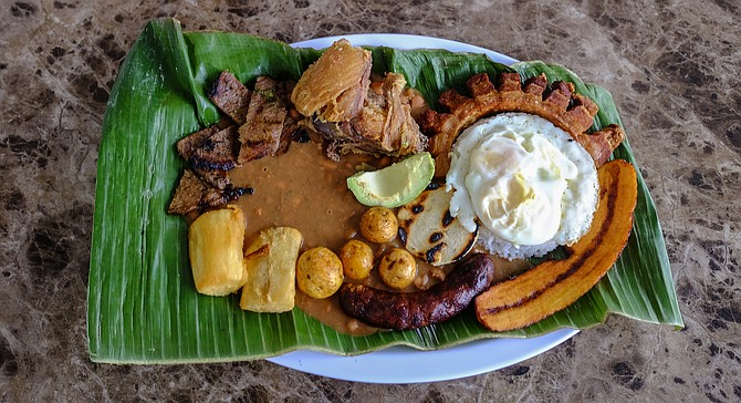 Clockwise from the top left corner: carne asada, fried chicken, crispy pork belly, fried plantain, sausage, and fried cassava. Fried egg, rice, arepa, potatoes, beans, and avocado in the center.