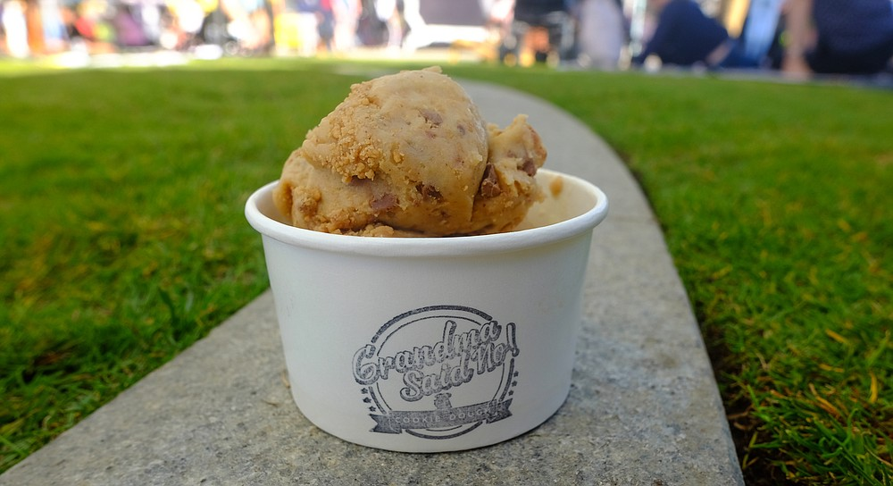 A scoop of raw, edible cookie dough mixed with chocolate peanut butter cups and salted caramel