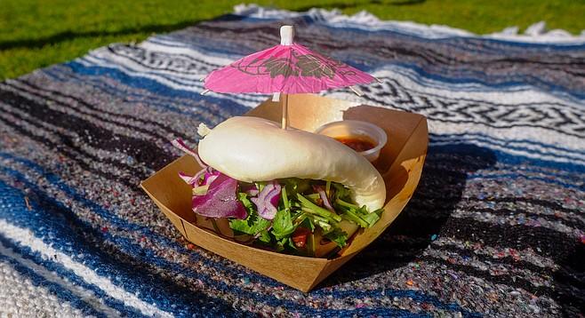Pork belly bao served with a cocktail umbrella, eaten on a falsa blanket