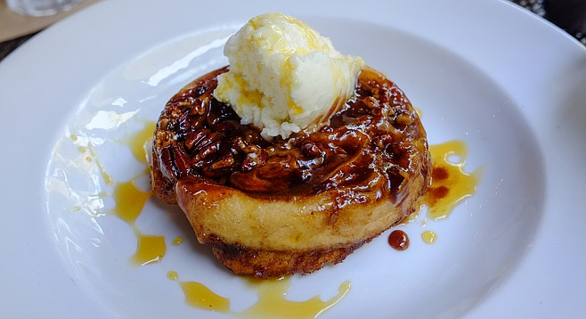 Skillet cooked pecan sticky bun topped with whipped cream cheese