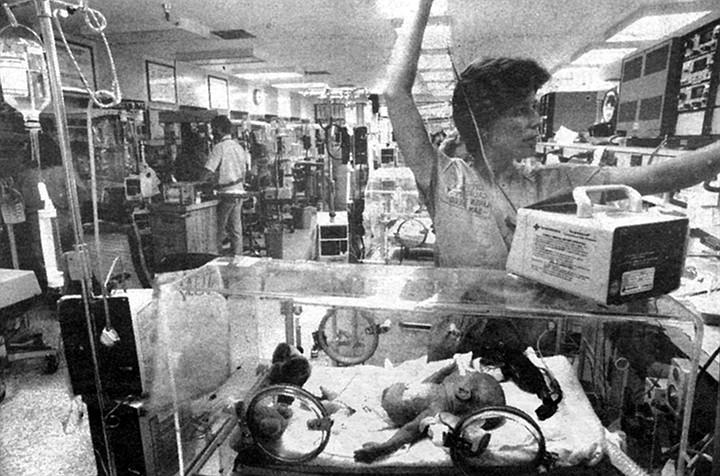 Nurse tending to baby in NICU