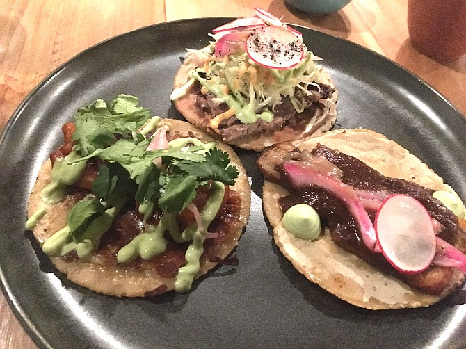 The taco menu includes clockwise from top, the carne asada with New York steak, the pork belly negro and the camarones a la diabla.