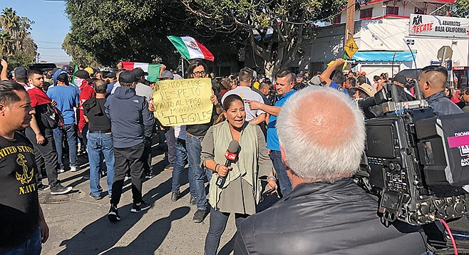 CNN reporter at Benito Juarez Field interviews an anti-migrant protester.