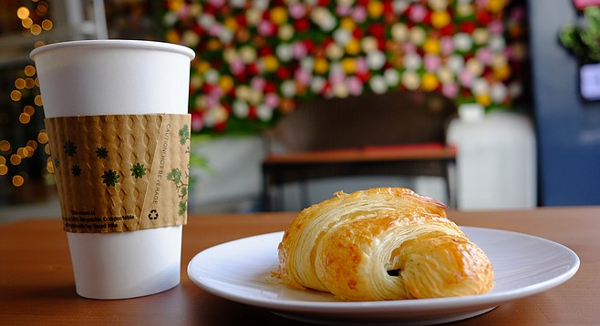 A coffee and croissant, with a wall of roses for background