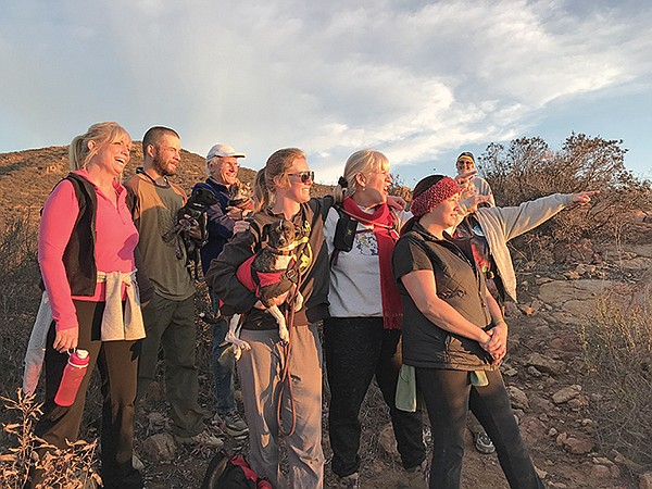 Kevin (3rd left), family, friends, dogs cheer moment of sun's return from depths