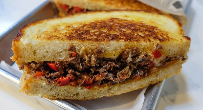 A Philly-style grilled cheese melt, with sliced beef and red peppers