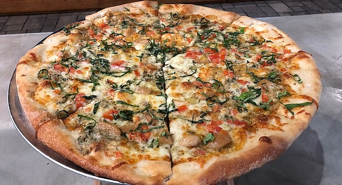 The Signature Surf Rider Pizza combines roast garlic, gorgonzola, tomatoes and basil.