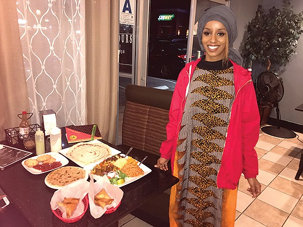 Farida's daughter stands beside my Somali meal