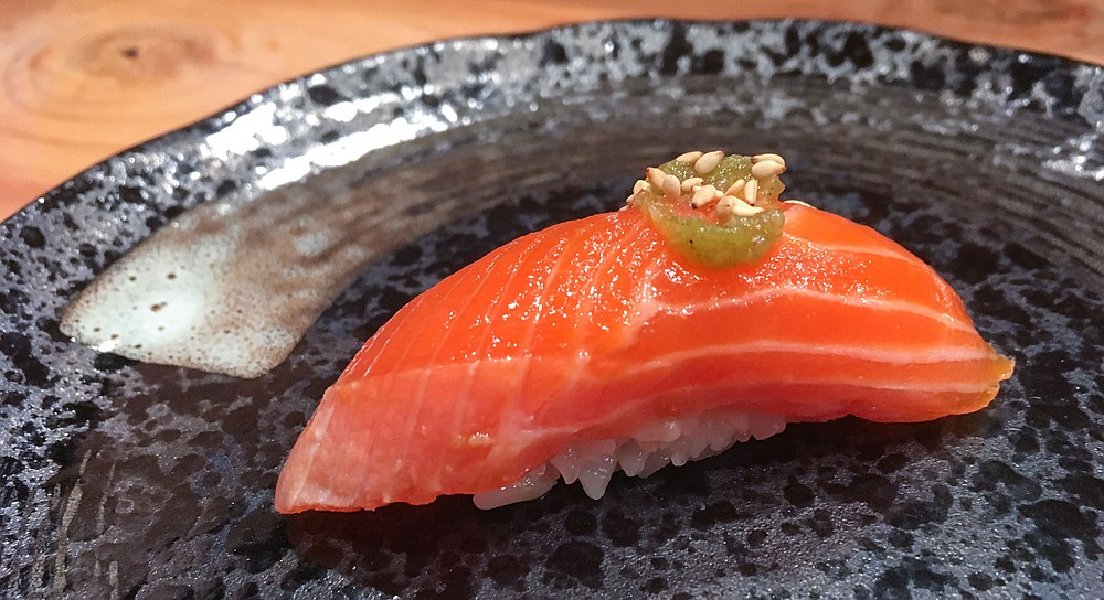Seared salmon garnished with a peppery yuzu sauce and sesame seeds