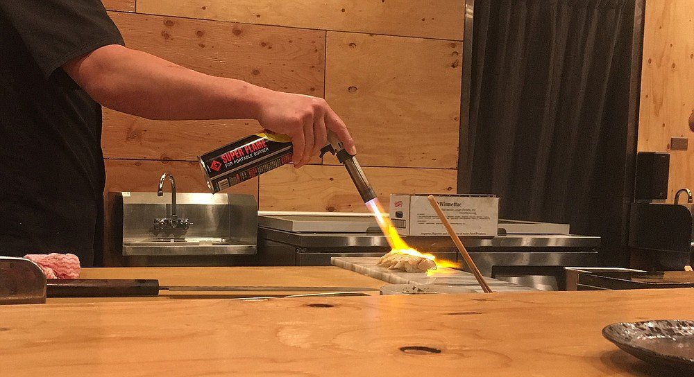 A sushi chef sears several pieces of black cod with a blowtorch.