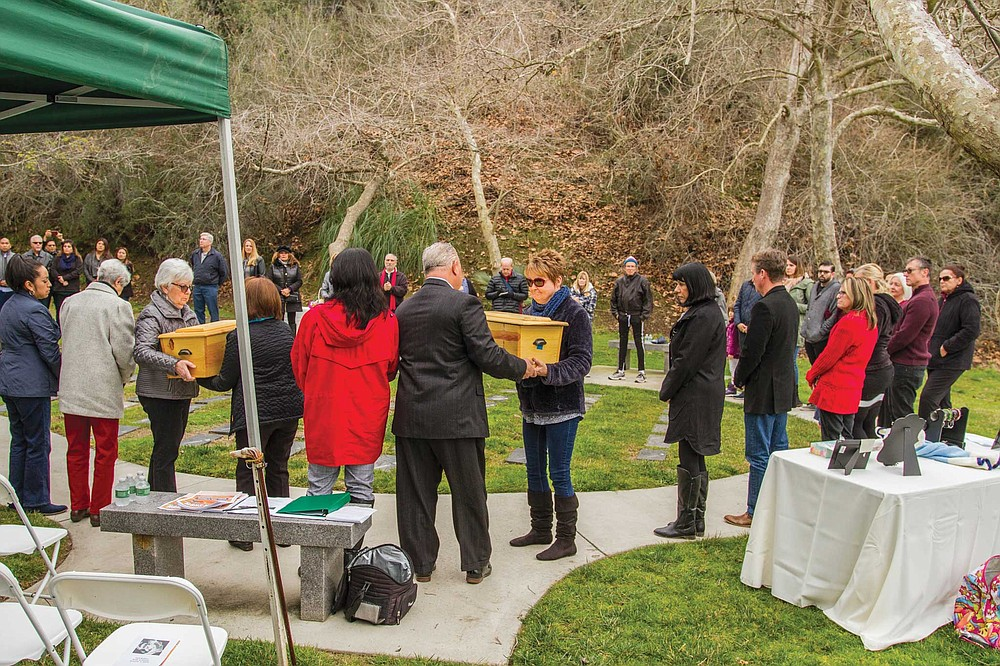 The Garden of Innocence at El Camino Memorial Park: first ritual, handing the caskets around. Holding each pine box from the handles or palming it from the bottom, people pass the pine coffins, bow heads, pause with closed eyes, whisper a prayer.