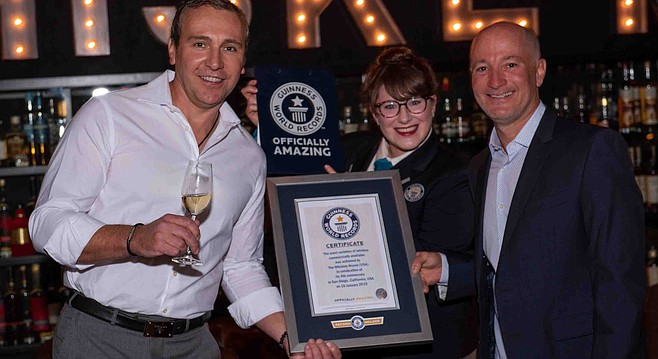 Whiskey House owners Alex Minaev and Ryan King celebrate as a Guinness judge awards a world record.