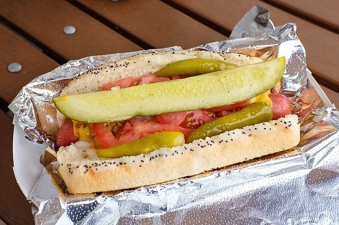 Chicago style hot dog on a poppy seed bun with mustard, onions, tomatoes, sports pepper, pickle, and celery salt