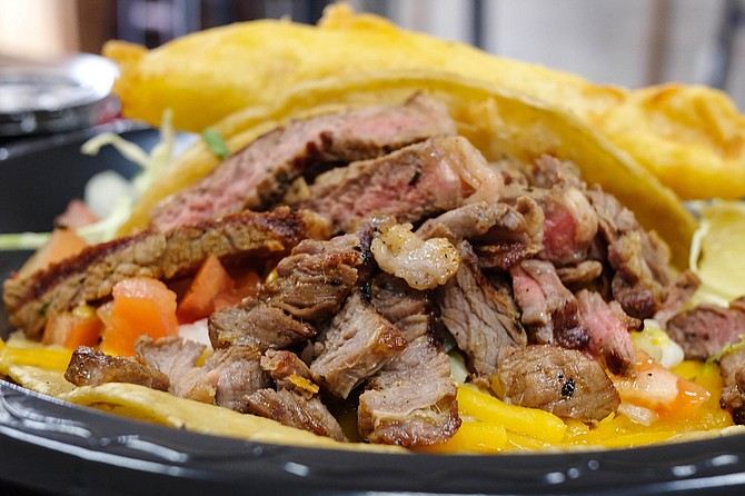 A pile of grilled ribeye with melted cheese on a corn tortilla