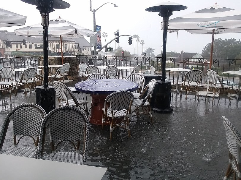 Puddles form as the rain comes down at Pacifica Breeze Cafe.